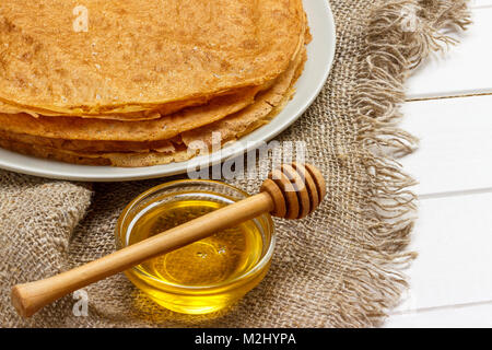 Pancakes on a white plate. Fresh honey in a jar. Wooden spoon for honey. Dessert. Healthy Breakfast. The table was - Stock Photo
