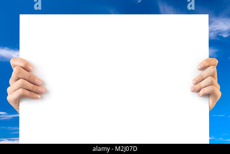 Hands holding a blank white board, blue sky background - Stock Photo