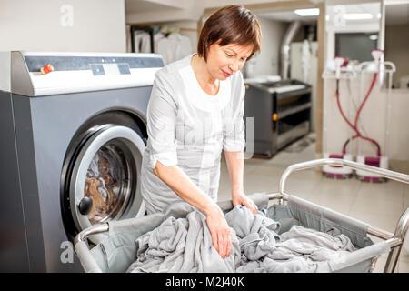 Senior washwoman in the laundry - Stock Photo