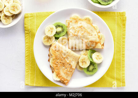 Crepes with banana and kiwi slices on plate. Top view, flat lay - Stock Photo
