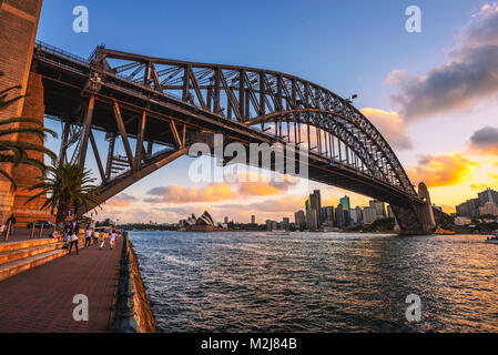 People walk under the Harbour Bridge with view of Sydney skyline