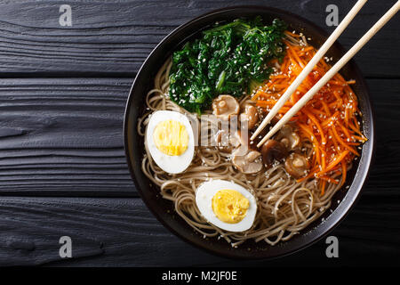 Asian Soba soup with vegetables, mushrooms, egg and sesame seeds close up in a bowl. horizontal top view from above - Stock Photo