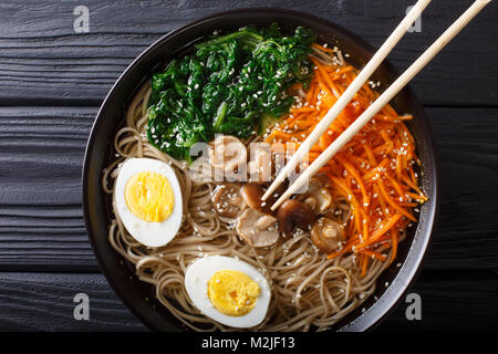 Buckwheat soup noodles with vegetables, shiitake mushrooms, egg and sesame close-up in a bowl. horizontal top view - Stock Photo