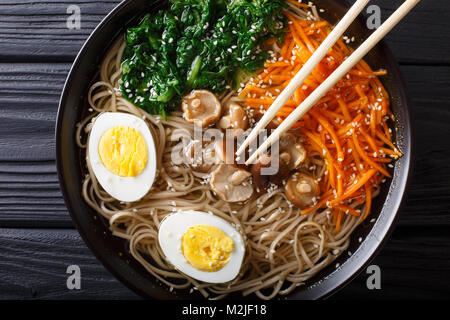 Soba noodles soup with vegetables, shiitake mushrooms, egg and sesame close-up in a bowl. Horizontal top view from - Stock Photo
