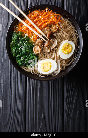 Asian Soba soup with vegetables, mushrooms, egg and sesame seeds close up in a bowl. Vertical top view from above - Stock Photo