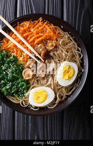 Buckwheat soup noodles with vegetables, shiitake mushrooms, egg and sesame close-up in a bowl. Vertical top view - Stock Photo