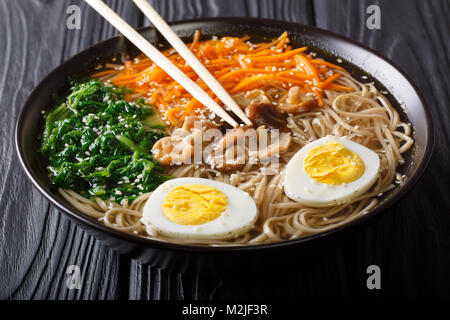 Asian food: soba soup with vegetables, shiitake mushrooms, egg and sesame seeds close up in a bowl. horizontal - Stock Photo