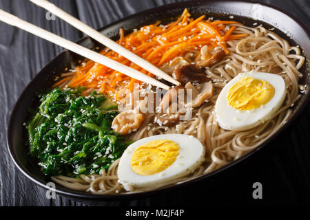Healthy food: soba soup with vegetables, shiitake mushrooms, egg and sesame seeds close up in a bowl. horizontal - Stock Photo