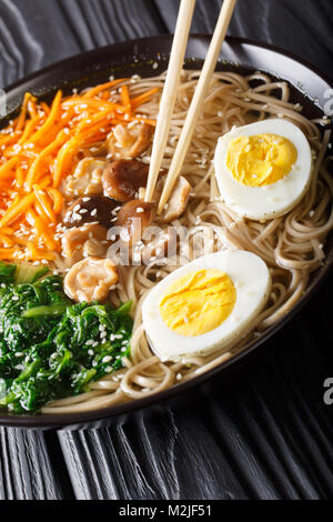 Buckwheat soup noodles with vegetables, shiitake mushrooms, egg and sesame close-up in a bowl. vertical - Stock Photo