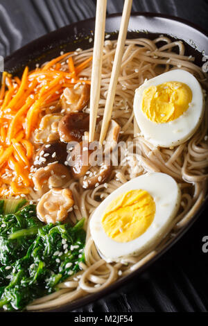Japanese Soba soup with vegetables, mushrooms, egg and sesame seeds close up in a bowl. vertical - Stock Photo