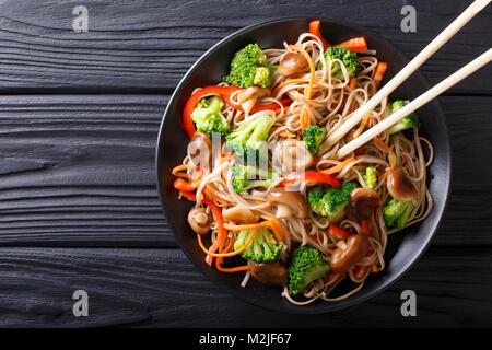fried soba noodles with mushrooms, broccoli, carrots, peppers closeup on a plate on a table. horizontal top view - Stock Photo