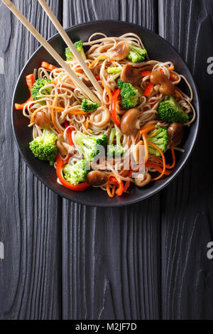 fried soba noodles with mushrooms, broccoli, carrots, peppers closeup on a plate on a table. Vertical top view from - Stock Photo