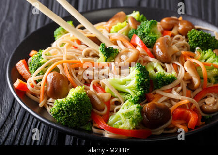 Japanese food: Soba noodles with mushrooms, broccoli, carrots, peppers close-up on a plate on the table. horizontal - Stock Photo