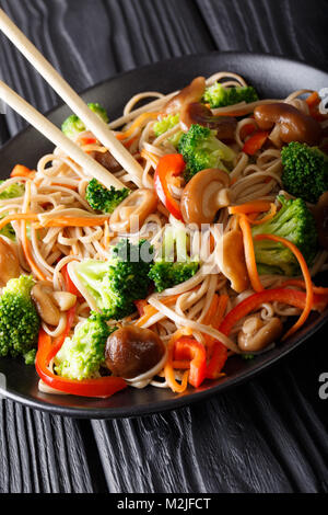fried soba noodles with mushrooms, broccoli, carrots, peppers closeup on a plate on a table. vertical - Stock Photo