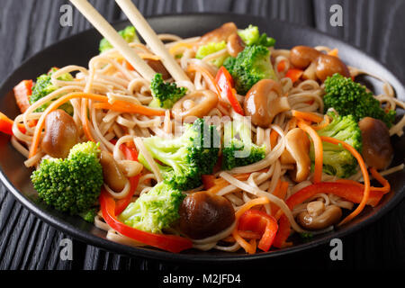 Buckwheat noodles with mushrooms and vegetables close-up on a plate. horizontal - Stock Photo