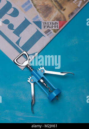 Blue Corkscrew on a blue background with a travel newspaper - Stock Photo