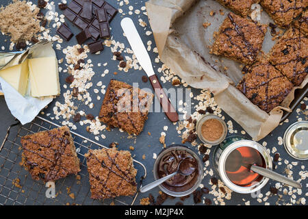 Homemade Flapjacks and ingredients on slate background - Stock Photo