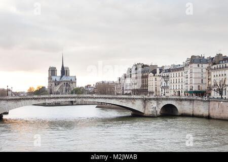 Apartments on Ile Saint Louis, Notre Dame Cathedral on Ile de la Cite and Pont de la Tournelle over Seine river, - Stock Photo