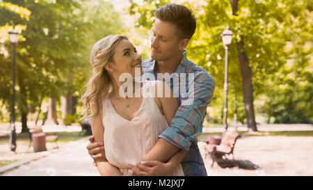 Cute guy and girl looking at each other with love tenderly, cuddling in park, stock footage - Stock Photo