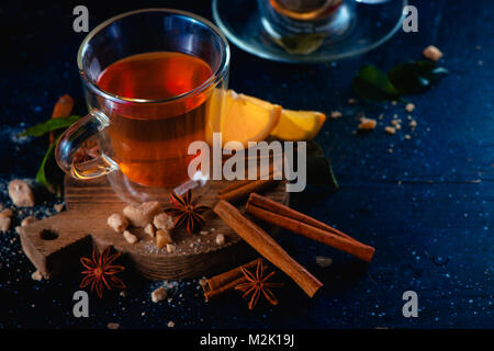 Double wall glass cup with hot lemon tea and cinnamon on a dark background. Spices for hot beverage. Cozy drink - Stock Photo