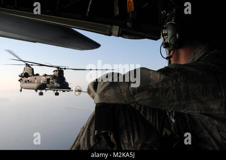A crewmember assigned to 67th Special Operation Squadron, based at RAF Mildenhall, England, watches as an U.S Army - Stock Photo