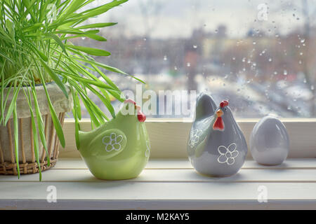 Cat grass and two ceramic hens with egg on a windowboard on a rainy day. This is early Springtime background with - Stock Photo