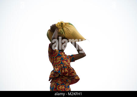 A young Dogon girl carries a sack back to her village on her head after attending a market in Dogon country, Mali, - Stock Photo