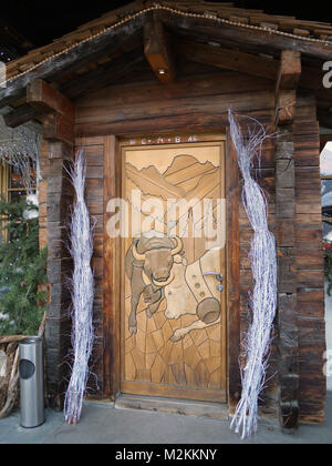 Door to Hotel Moiry in Grimentz detailing the famous fighting cows of the local area, Val d'Herens. The cows fight - Stock Photo