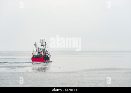 A large fishing boat heads out into the pristine whiteness of snow clouds in Fowey, Cornwall. Near white out conditions - Stock Photo