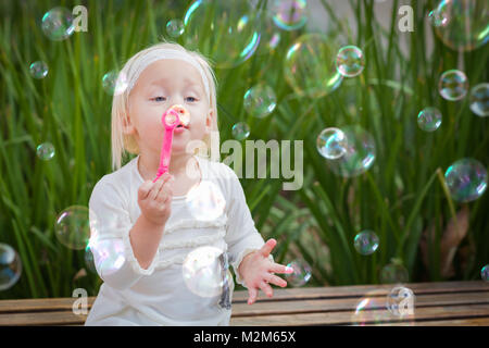 Adorable Little Girl Sitting On Bench Having Fun With Blowing Bubbles Outside. - Stock Photo