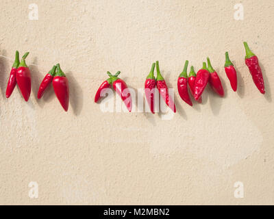 group of fresh ripe chili pepper hanging to dry in the sun on a string. Plastered wall in background - Stock Photo