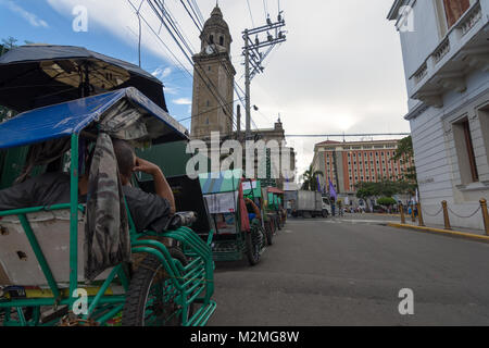 A queue of pedal taxi's with resting drivers out side of the Manila Cathedral in the Old Town, Spanish Quarter, - Stock Photo