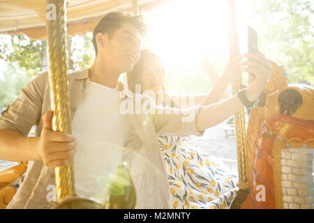 Young lovers riding merry rides on the playground - Stock Photo