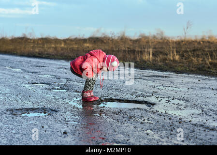 Little girl looking into puddle, children, unforgettable moments, fun with father, village life. Concept - happy - Stock Photo