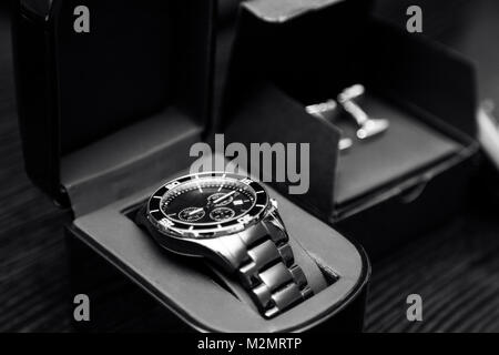 Close up of new elegant expensive stainless steel silver chrome men's classic design watches in a box near cufflinks - Stock Photo