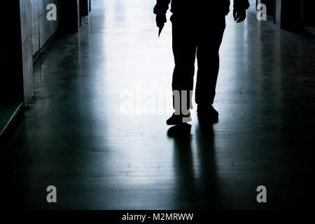 Blurry trap in dark alley in the night, silhouette of a man from waist down holding sharp object in hand while approaching