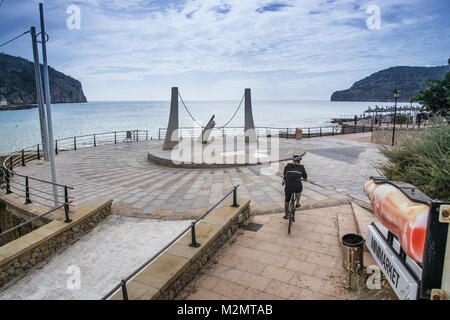 CAMP DE MAR, MALLORCA, SPAIN ON OCTOBER 25, 2013: Bicyclist races downhill near sundial sculpture by closed food - Stock Photo