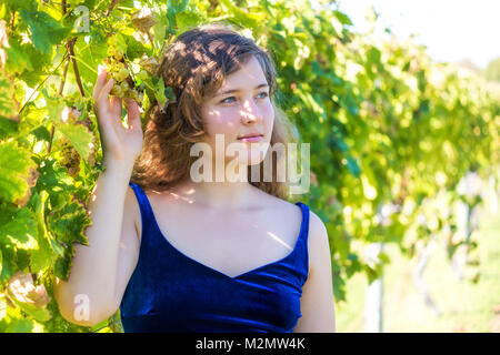 Closeup portrait of elegant young woman's face by vineyard winery grapevine leaves green in Virginia holding grapes, - Stock Photo