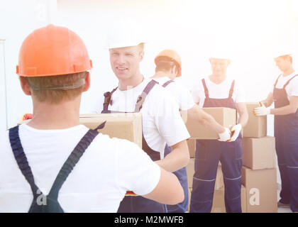 Happy male movers in uniform carrying boxes - Stock Photo