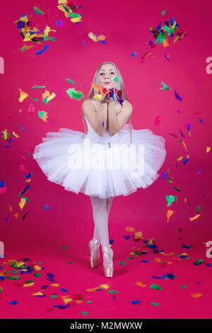 Pretty blonde ballerina in tutu skirt blowing colorful feathers on pink backdrop. - Stock Photo