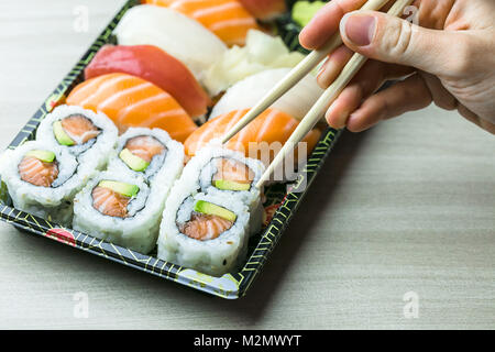 Hand using chopsticks pick Sushi, Sashimi and Futomaki rolls.  Fresh made Sushi set with salmon, prawns, wasabi - Stock Photo