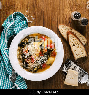 Curly kale (or cavolo nero) and barley soup. Winter Vegetable Soup on a wooden table and fresh homemade bread - Stock Photo