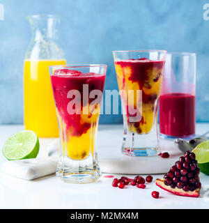 two glasses of alcoholic cocktail with orange liqueur, freshly squeezed pineapple and pomegranate juice and lime - Stock Photo