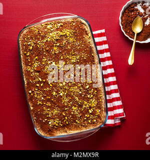 traditional Italian dessert with coffee, cocoa and mascarpone cheese Tiramisu cake in an oven pan on a red. sprinkled - Stock Photo
