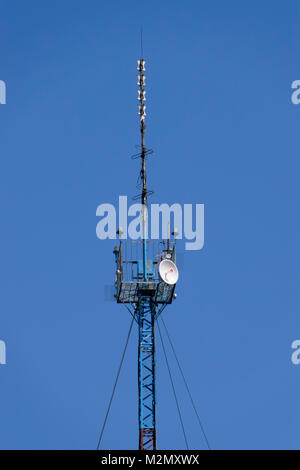 Communication tower with repeaters and satellite dish. - Stock Photo