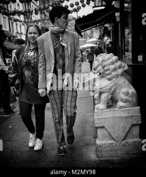 Black & White Photograph of a young couple walking hand in hand in China Town, Soho, Central London, England, United - Stock Photo