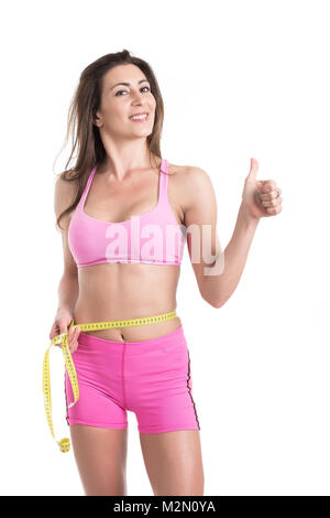 Close up of female hands measuring waist with measuring yellow tape. Fit and healthy woman on white background - Stock Photo