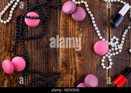 Gentle biscuits macaroons on a wooden background with the attributes of a cosmetic bag. View from above. - Stock Photo