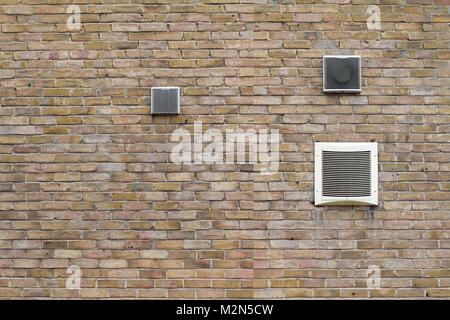 horizontal front view of air conditioning vents of different sizes on brick wall - Stock Photo