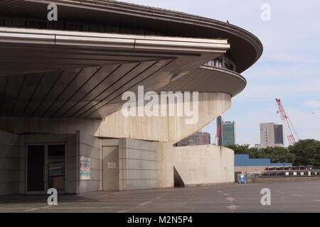 The Fumiko Maki-designed Tokyo Metropolitan Gymnasium with cranes on the 2020 Tokyo Olympic Stadium construction - Stock Photo